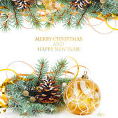 Christmas tree branch with gold serpentine and yellow sphere on  — Stock Photo