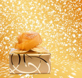 Gift box in gold wrapping paper on a beautiful  abstract backgro — Stock Photo