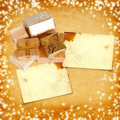 Gift box in gold wrapping paper on vintage cardboard background  — Stock Photo