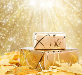 Gift box in gold wrapping paper with autumn leaves on the abstra — Stock Photo