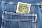One dollar bill sticking in the back pocket of denim blue jeans — Foto Stock