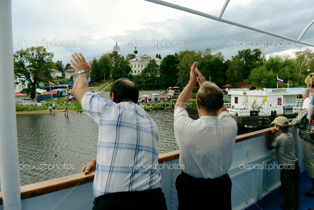 Passengers of the sailing ship say goodbye to the settlement Myshkin which iis located on the river bank Volga.   Stock Photo #12779906