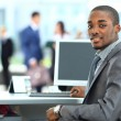 Portrait of a happy African American entrepreneur displaying computer laptop in office — Stock Photo #17383145