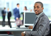 Portrait of a happy African American entrepreneur displaying computer laptop in office — Stock Photo