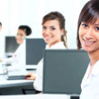 Business woman with a computer at the office with a group behind — Stock Photo