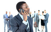 Smiling handsome business man using cell phone with colleagues in background — Stock Photo