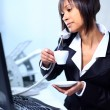 Businesswoman sitting at the table in office lobby, drinking coffee. — Stock Photo #22911486
