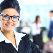 Business woman standing with her staff in background — Stock Photo #22922608