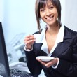 Businesswoman sitting at the table in office lobby, drinking coffee. - Stock Photo
