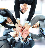 Small group of business joining hands, low angle view. — Stock Photo