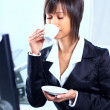 Businesswoman sitting at the table in office lobby, drinking coffee. — Stock Photo