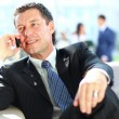 Royalty-Free Stock Photo: Concentrating businessman on call, coworkers talkling in background