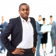 Stock Photo: Portrait of smart AfricAmericbusiness msmiling with colleagues in background