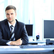 Young businessman working in office, sitting at desk — Stock Photo #30244091