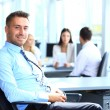 Portrait of young businessman in office with colleagues in the background — Stock Photo #30244789