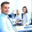 Portrait of young businessman in office with colleagues in the background — Stock Photo