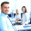 Stock Photo: Portrait of young businessman in office with colleagues in the background