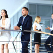 Portrait of positive business group standing on stairs of modern office — Stock Photo