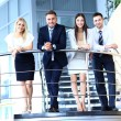 Stock Photo: Portrait of positive business group standing on stairs of modern office
