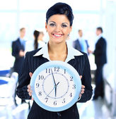Young attractive business woman holding clock — Stock Photo