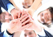Small group of business people joining hands, low angle view. — Stock Photo