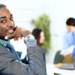 Portrait of smiling African American business man with executives working in background — Stock Photo