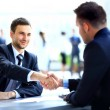 Stock Photo: Two business colleagues shaking hands during meeting