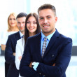 Smiling business people standing together in line in a modern office — Stock Photo #41439257