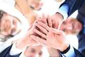 Small group of business people joining hands, low angle view — Stock Photo