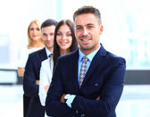 Smiling business people standing together in line in a modern office — Stock Photo