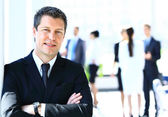 Happy businessman standing in front of his colleagues in office — Stock Photo