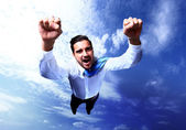 Happy businessman flying in the sky — Stok fotoğraf