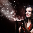 Beautiful girl blowing magic stars — Stock Photo #41440075
