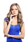 Young woman in blue dress posing in studio — Stock Photo