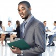 African american businessman in modern office with colleagues on background — Stock Photo #41649421