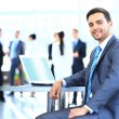 Happy young businessman using laptop in business building — Stock Photo #41649451