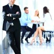 Businessman standing with his team — Stock Photo