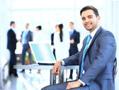 Happy young businessman using laptop in business building — Stock Photo