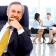 Successful business man standing with his staff in background at office — Stock Photo #42436631