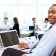 Portrait of a happy African American entrepreneur displaying computer laptop — Stock Photo #42436633