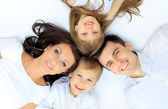 Family lying down on their bed at home — Stock Photo