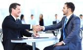 Business colleagues sitting at a table during a meeting with two male executives shaking hands — Stock Photo