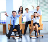 Happy office employees having fun at work in an office chair race — Stock Photo