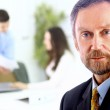 Closeup portrait of mature business man with colleagues at the back — Stock Photo #5109144