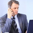 Handsome business guy working on cellphone and laptop together while at wor — Stock Photo #5637897