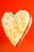 Heart Shaped Jam Sandwich on Red Background — Stock Photo