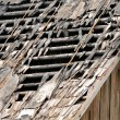 Broken Roof of Old Abandoned Wooden House - Stock Photo