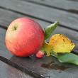 Red Apple with Leaves on Wooden Table — Stock Photo #13768650