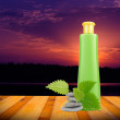 Royalty-Free Stock Photo: Green Cosmetic Bottle with Nettle and Zen Stones on Wooden Deck at Sunset