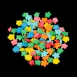 Flower-Shaped Colorful Sugar Sprinkles (Edible Cake Decorations) on Black Background — Stock Photo